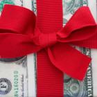 A gift wrapped in dollar bills tied with a red ribbon